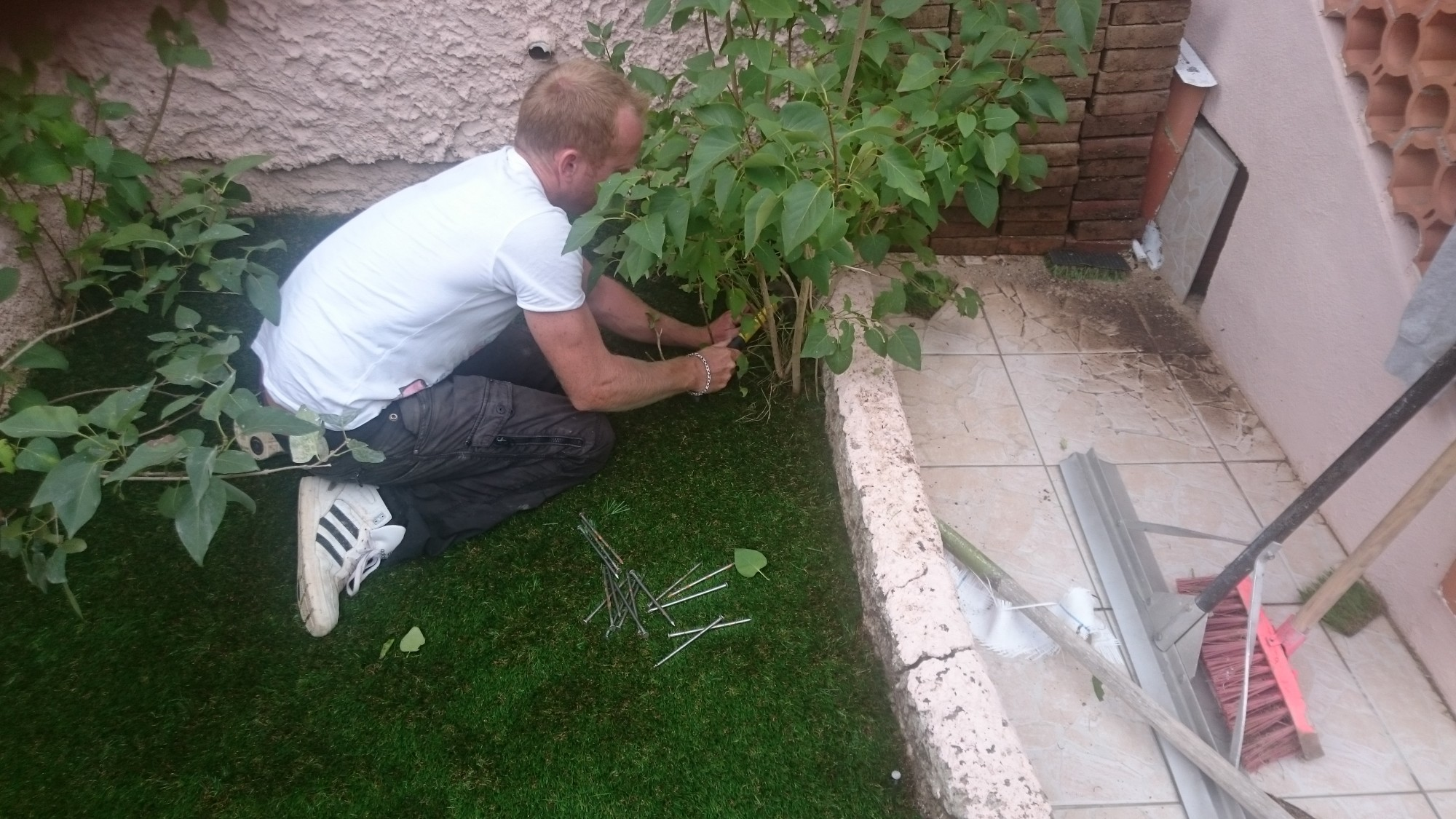 Fixation de la périphérie du gazon synthétique dans un jardin à Nice