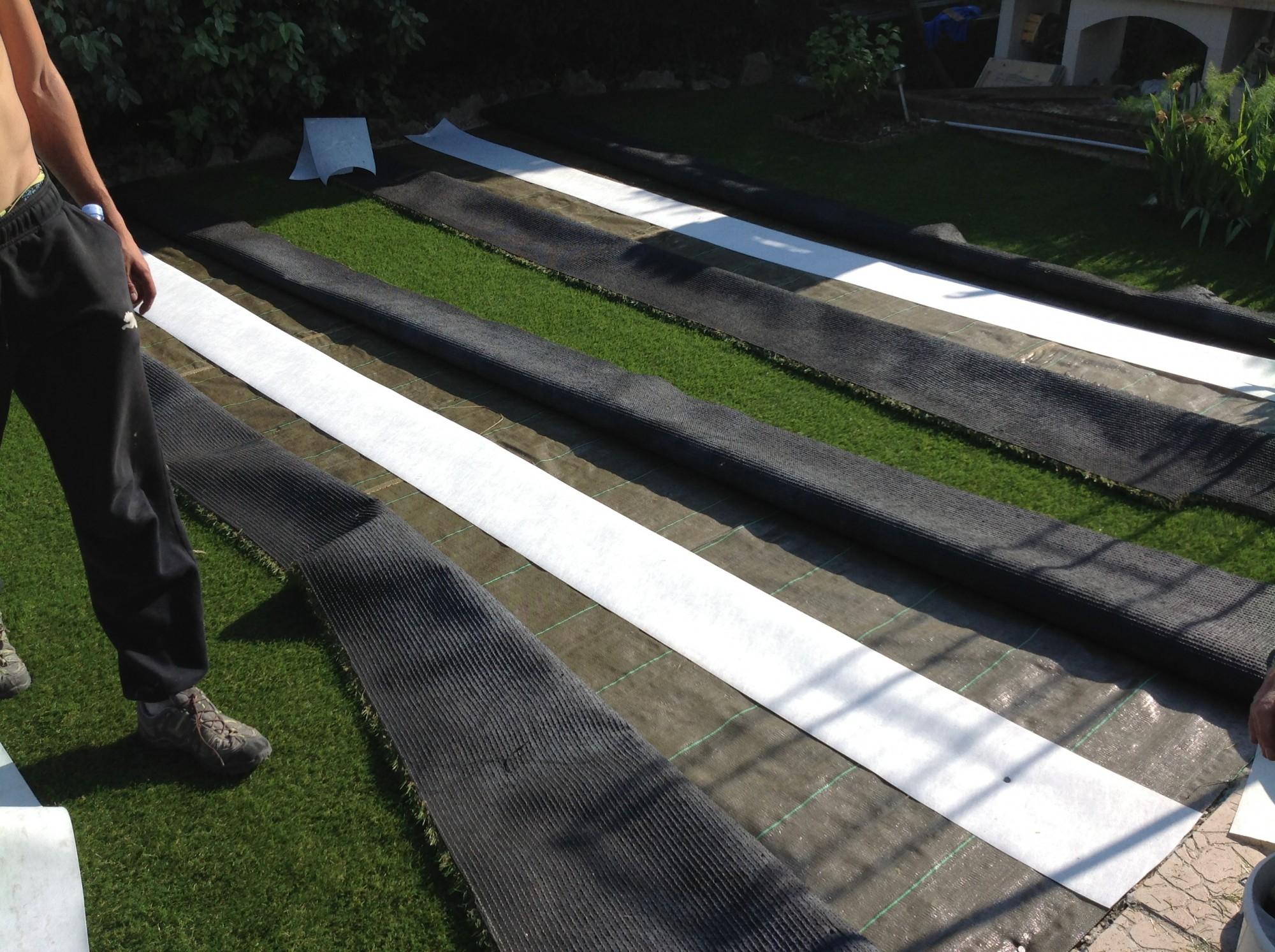 Mise en place des bandes de pontage lors d'une installation de gazon synthétique à Toulon